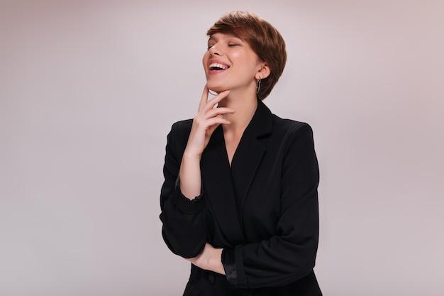 Portret kobiety w czarnej kurtce, śmiejąc się na na białym tle. szczęśliwa młoda krótkowłosa dama uśmiecha się na białym tle