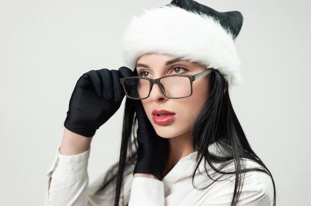 Portret kobiety w czarnym garniturze z okularami i czarną czapką mikołaja