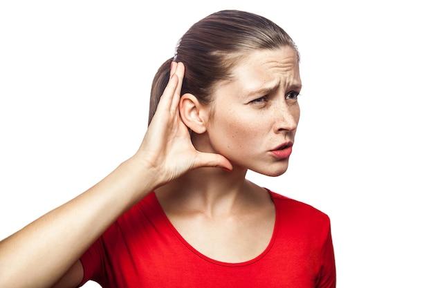 Portret kobiety w czerwonej koszulce z piegami próbuje słuchać. strzał studio. na białym tle.