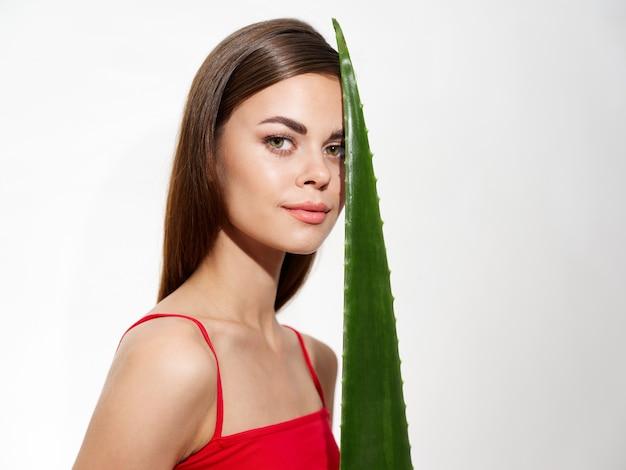 Portret kobiety w czerwonej koszulce z zielonym liściem aloesu przy twarzy na jasnym tle