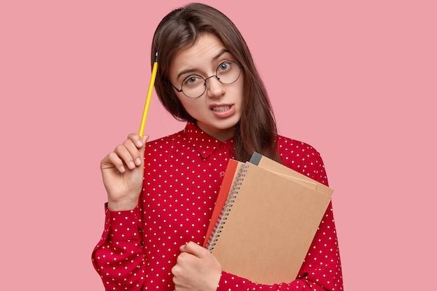 Portret kobiety w czerwonej koszuli i okrągłych okularach, trzymając notesy