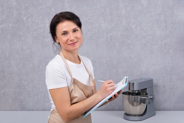 Portret kobiety w fartuch kuchenny z dokumentami w dłoniach. cook wypisuje receptę.