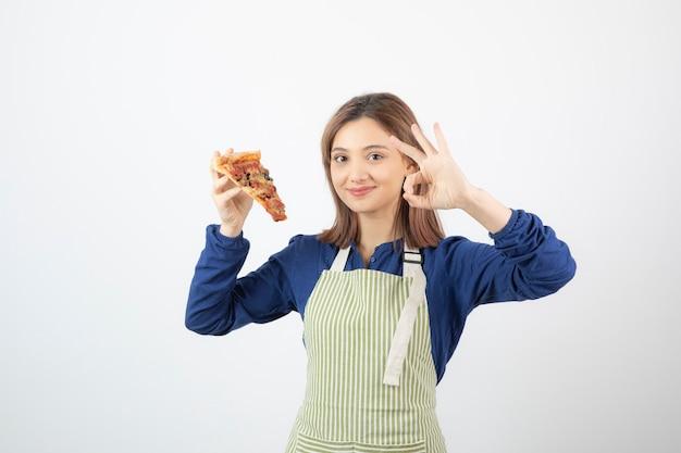 Portret kobiety w fartuchu pokazujący kawałek pizzy na białym tle