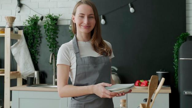 Portret kobiety w fartuchu stoi z talerzami w dłoniach w kuchni