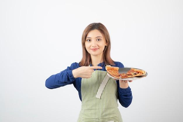 Portret kobiety w fartuchu, wskazując na kawałek pizzy na białym tle