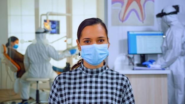 Portret kobiety w gabinecie dentystycznym, patrząc na kamery sobie maskę siedzi na krześle w poczekalni kliniki podczas pracy lekarza. koncepcja nowej normalnej wizyty u dentysty w epidemii koronawirusa.