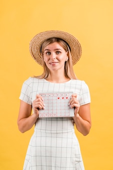 Portret kobiety w kapeluszu, trzymając jej kalendarz menstruacyjny