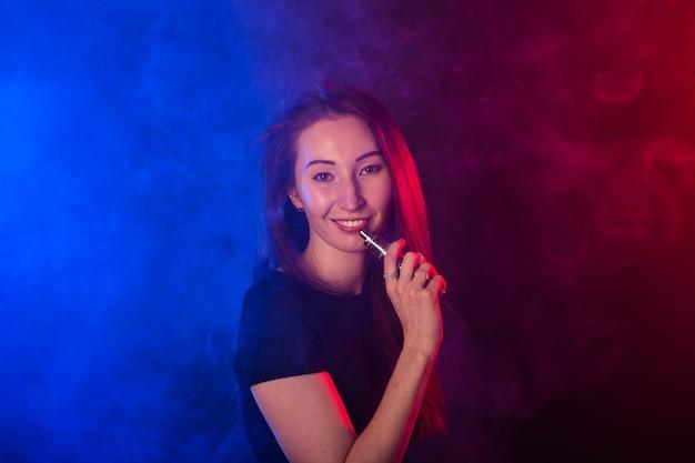 Portret kobiety w kolorowym neonowym dymie z vape lub elektronicznego papierosa.