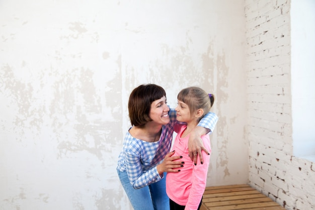 Portret kobiety w koszuli w kratę, obejmując córkę