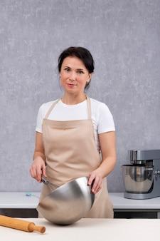 Portret kobiety w kuchni w fartuch kuchenny. proces gotowania. rama pionowa.