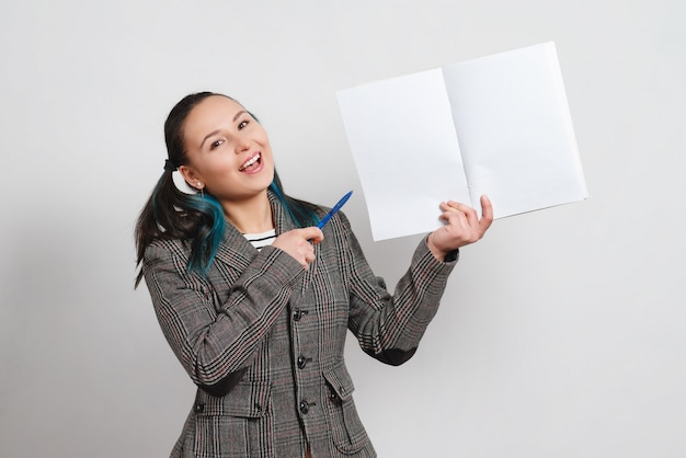 Portret kobiety w kurtce na lekkiej ścianie. trzyma notatnik z miejsca kopiowania i pokazuje długopis.