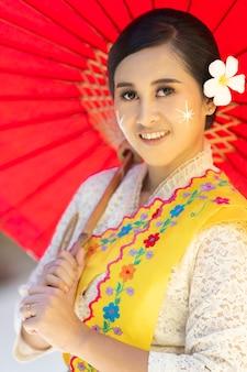 Portret kobiety w lokalnym stroju birmańczyka, nosi czerwony parasol.