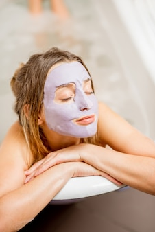 Portret kobiety w masce na twarz leżącej w wannie retro w łazience