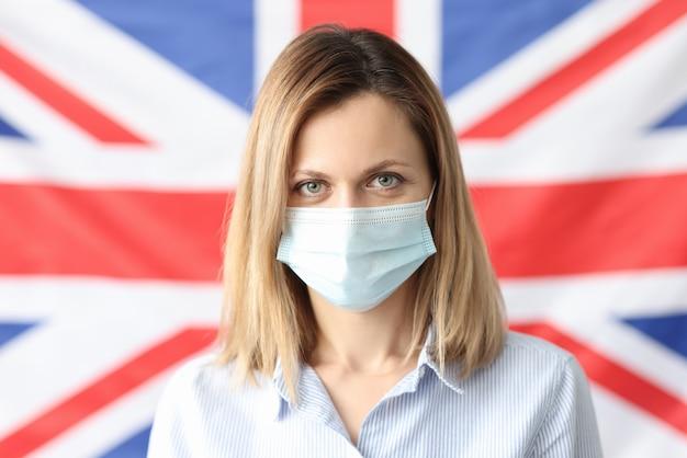 Portret kobiety w masce ochronnej na tle flagi brytyjskiej. brytyjski szczep