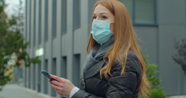 Portret kobiety w medycznej masce ochronnej wpisując telefon komórkowy na zewnątrz.