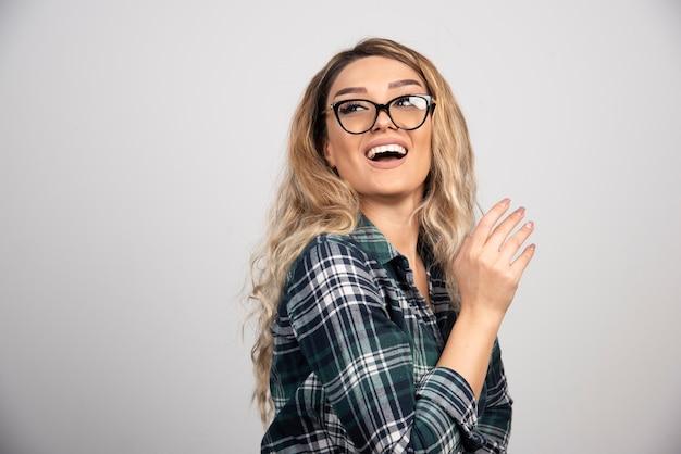 Portret kobiety w modnych okularach uśmiechający się szczęśliwie.