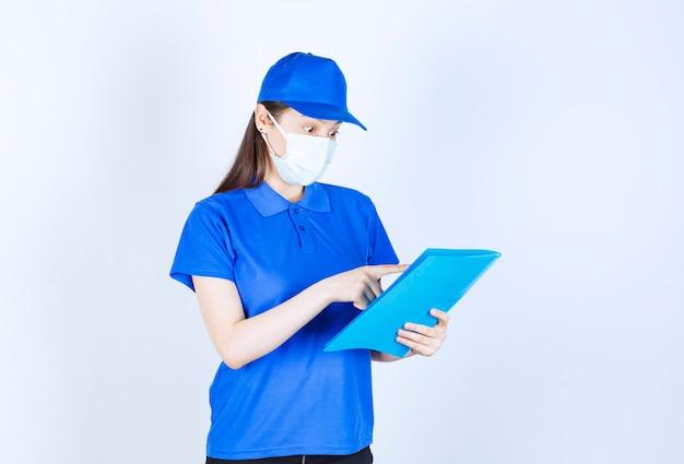 Portret kobiety w mundurze i masce medycznej trzymającej folder