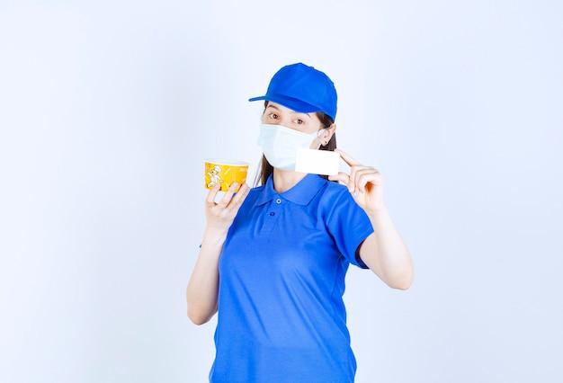 Portret kobiety w mundurze i masce medycznej trzymającej kartę