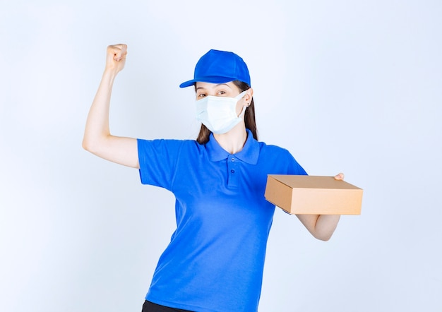 Portret kobiety w mundurze i masce medycznej trzymającej papierowe pudełko