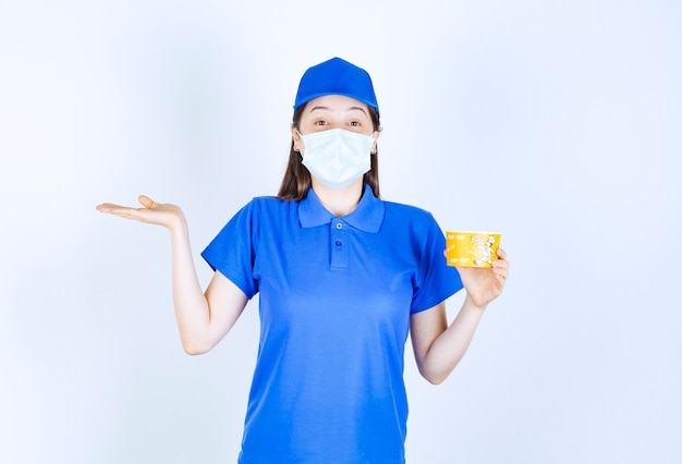 Portret kobiety w mundurze i masce medycznej trzymającej plastikowy kubek