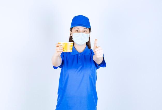 Portret kobiety w mundurze i masce medycznej z plastikowym kubkiem pokazującym kciuk w górę