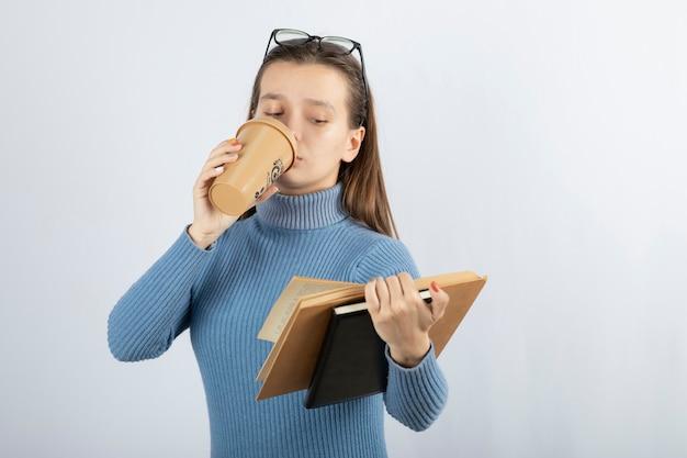 Portret kobiety w okularach czyta książkę przy filiżance kawy.