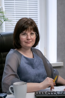Portret kobiety w okularach, dyrektor firmy w gabinecie podczas pracy. biznesmenka. sekretarz na stanowiskach pracy.
