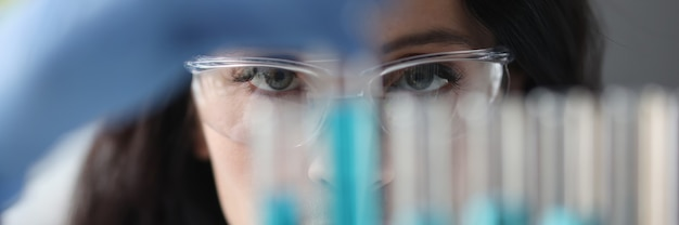 Portret kobiety w okularach, która patrzy na probówki z płynnymi badaniami i rozwojem