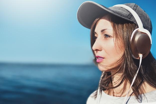 Portret kobiety w okularach przeciwsłonecznych w czapce, która lubi muzykę na tle morza.