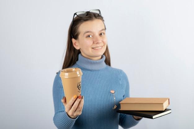 Portret kobiety w okularach trzymającej dwie książki i filiżankę kawy.