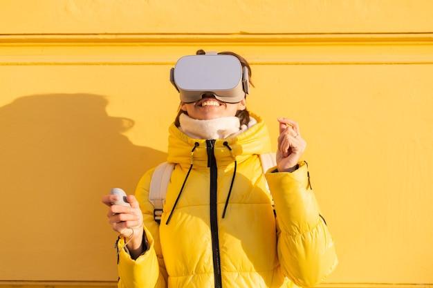 Portret kobiety w okularach wirtualnej rzeczywistości na ulicy na żółtej ścianie w jasnym świetle słonecznym zimą w ciepłych ubraniach