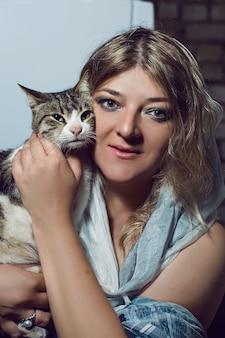 Portret kobiety w pelerynie przytulającej kota w studio