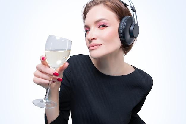 Portret kobiety w profesjonalnych słuchawkach z lampką wina w dłoni. białe tło. koncepcja dj-a. różne środki przekazu