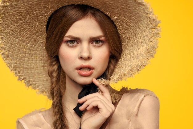 Portret kobiety w słomkowym kapeluszu na żółtej przestrzeni przycięty widok letniej sukni modelu warkocze romansu.