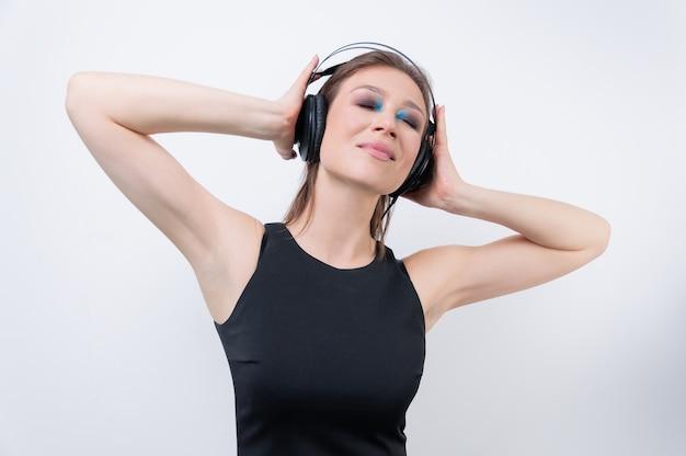 Portret kobiety w słuchawkach. zanurzenie w świat muzyki. koncepcja dj. różne środki przekazu