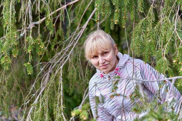 Portret kobiety w średnim wieku o blond włosach wśród gałęzi jodły