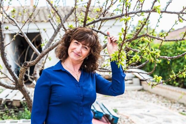 Portret kobiety w średnim wieku patrząc na drzewo w swoim ogrodzie