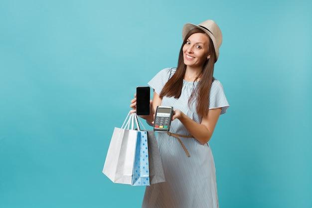 Portret kobiety w sukni, kapeluszu trzymającego torby z zakupami po zakupach, bezprzewodowy terminal płatniczy nowoczesny bank do przetwarzania i nabywania płatności kartą kredytową na białym tle na niebieskim pastelowym tle.