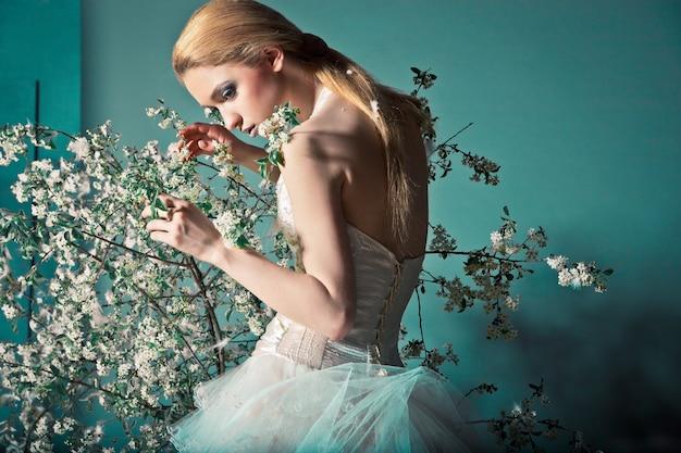 Portret kobiety w sukni ślubnej za gałęziami z kwiatami