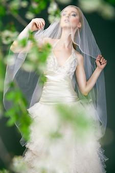 Portret kobiety w sukni ślubnej za zielonymi gałązkami z kwiatami