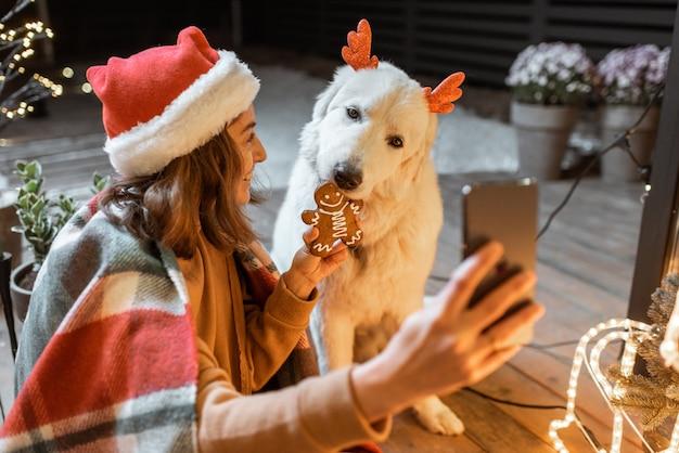 Portret kobiety w świątecznym kapeluszu i kracie ze swoim uroczym psem świętującym święta nowego roku w domu, karmiącym psa piernikowymi ciasteczkami i robiącym zdjęcie selfie