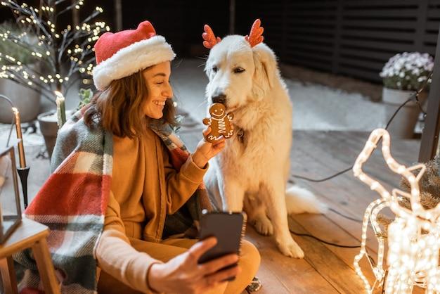 Portret kobiety w świątecznym kapeluszu i kratce ze swoim uroczym psem świętującym święta noworoczne na pięknie udekorowanym tarasie w domu, karmiącego psa piernikowymi ciasteczkami