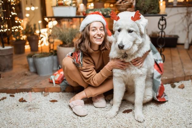 Portret kobiety w świątecznym kapeluszu z uroczym psem świętującym święta noworoczne, siedzącej razem na pięknie udekorowanym tarasie w domu