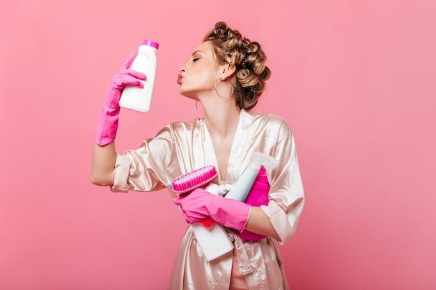 Portret kobiety w szlafroku, szczęśliwie pozowanie na różowej ścianie z detergentami