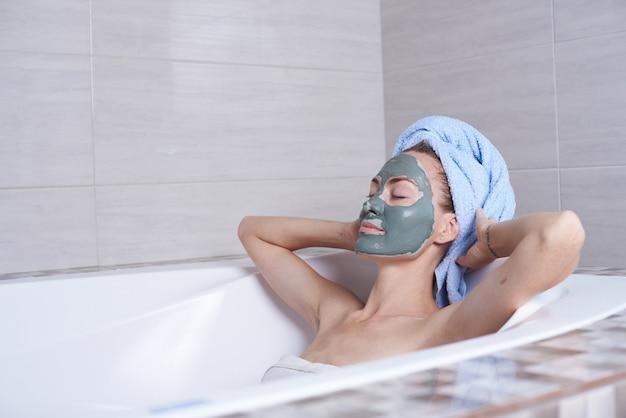 Portret kobiety w twarzy alginianu maska leżącego w retro kąpieli w łazience