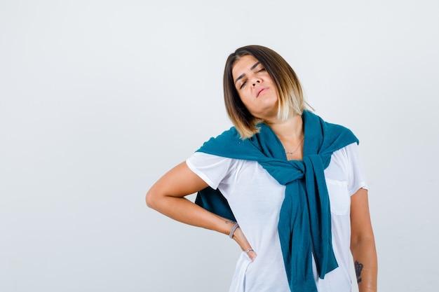 Portret kobiety w wiązanym swetrze cierpiącej na ból pleców w białej koszulce i wyglądającej na zmęczonego widoku z przodu