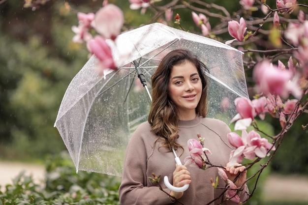 Portret kobiety w wieku 33-35 lat w pobliżu drzewa magnolii