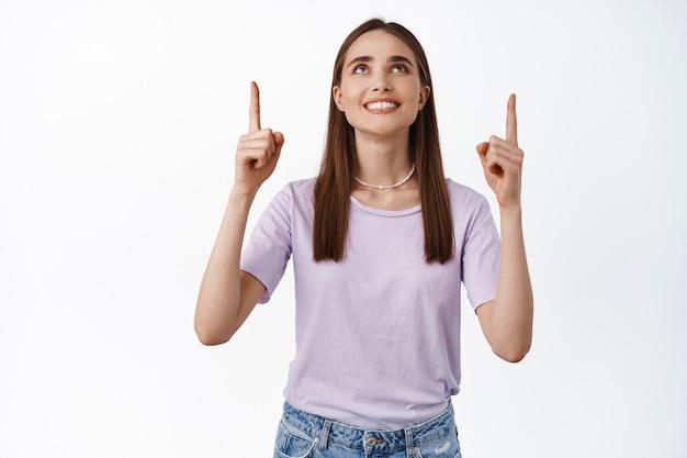 Portret kobiety wskazującej i patrzącej w górę z zadowolonym białym uśmiechem dokonującej wyboru, stojącej na białym w t-shirt