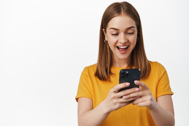 Portret kobiety wygląda na zaskoczonego i podekscytowanego na ekranie smartfona, otrzymuje przyjemne powiadomienie, ogląda wideo na telefonie komórkowym