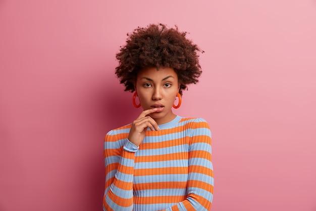 Portret kobiety wygląda poważnie, trzyma palec przy ustach, ma spokojny wyraz twarzy, kręcone włosy, ubrana w sweter w paski, odizolowany na różowej ścianie. zdecydowana kobieta zastanawia się nad propozycją